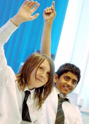Two secondary school children with hands up