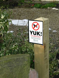 yuk dog fouling sign on post in a park