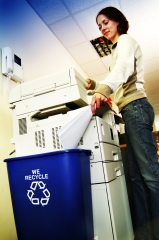 woman recycling paper into a blue recycling bin