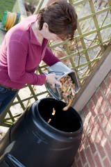 Women pouring waste into a compost bin