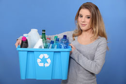 Woman holding recycling bin filled with bottles