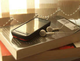 mobile phone with headphones and a book on a table