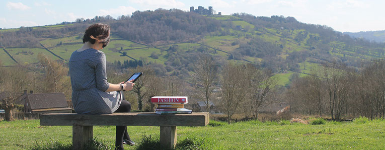 Woman reading a book overlooking Riber Castle