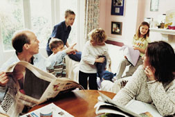 Photograph of a busy family - parents and four children in a dining room