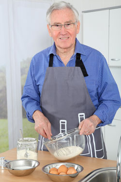 Elderly man whisking eggs in the kitchen